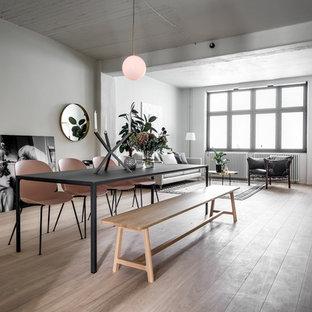 Bild på en minimalistisk matplats med öppen planlösning, med vita väggar, ljust trägolv och beiget golv