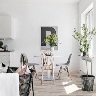 Foto på en minimalistisk matplats, med vita väggar, ljust trägolv och beiget golv