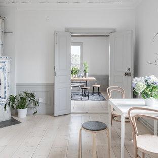 Foto på en nordisk matplats, med ljust trägolv, beiget golv, vita väggar, en öppen hörnspis och en spiselkrans i trä