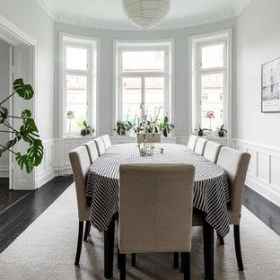 Skandinavisk inredning av en mellanstor separat matplats, med vita väggar, målat trägolv och svart golv