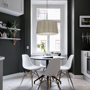Example of a mid-sized danish light wood floor and beige floor kitchen/dining room combo design in Stockholm with black walls