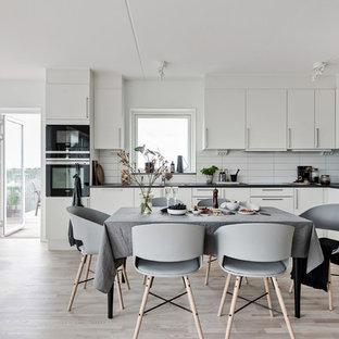Inspiration för minimalistiska matplatser med öppen planlösning, med vita väggar, ljust trägolv och beiget golv