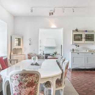 Modelo de comedor romántico, grande, cerrado, sin chimenea, con paredes blancas, suelo de ladrillo y suelo rojo