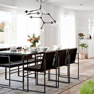 Inredning av ett modernt stort kök med matplats, med vita väggar, ljust trägolv och beiget golv