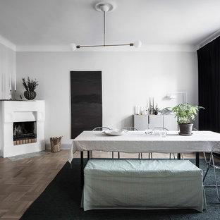 Nordisk inredning av en mellanstor separat matplats, med vita väggar, mellanmörkt trägolv, en öppen hörnspis, en spiselkrans i gips och beiget golv