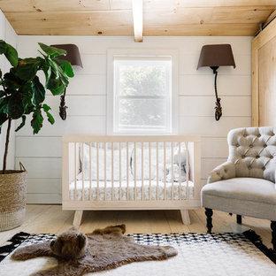 Diseño de habitación de bebé neutra de estilo de casa de campo, pequeña, con paredes blancas y suelo de madera clara