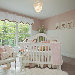 Nursery - traditional girl carpeted and beige floor nursery idea in Boston with pink walls