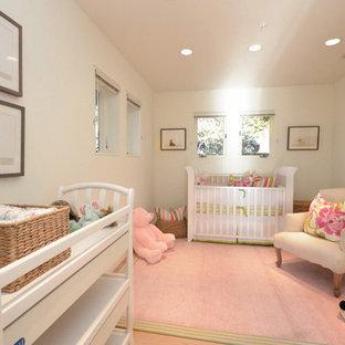 Exemple d'une chambre de bébé fille chic avec un mur blanc, un sol en bois clair et un sol rose.