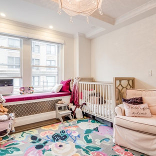 This is an example of a medium sized classic nursery for girls in New York with white walls, dark hardwood flooring and brown floors.