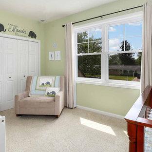 Modelo de habitación de bebé neutra clásica renovada, de tamaño medio, con paredes verdes, moqueta y suelo beige