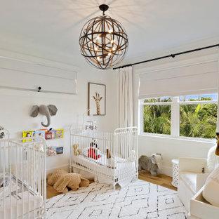 Modelo de habitación de bebé neutra tradicional renovada, grande, con paredes rojas, suelo de madera clara y suelo beige