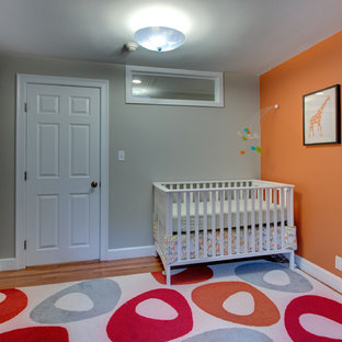 Imagen de habitación de bebé neutra tradicional renovada con parades naranjas y suelo de madera en tonos medios