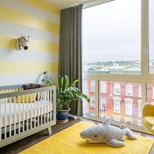 Cette photo montre une chambre de bébé neutre tendance avec un mur jaune, un sol en bois foncé et un sol marron.