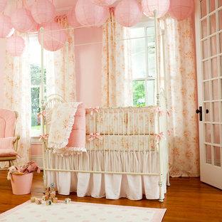 Inspiration pour une chambre de bébé fille style shabby chic avec un mur rose, un sol en bois brun et un sol orange.