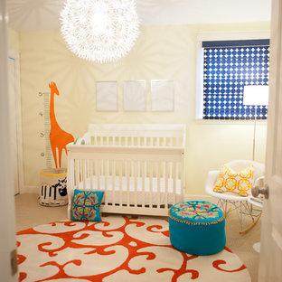 Cette image montre une chambre de bébé neutre traditionnelle de taille moyenne avec un mur jaune et moquette.