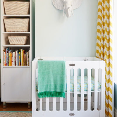 Inspiration for a transitional gender-neutral medium tone wood floor nursery remodel in New York with blue walls