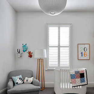This is an example of a large contemporary gender-neutral nursery in Melbourne with white walls, carpet and grey floor.
