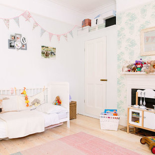 Photo of a medium sized classic nursery in London with grey walls, light hardwood flooring and beige floors.