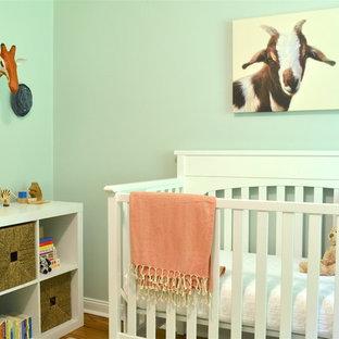 Diseño de habitación de bebé niño tradicional renovada, pequeña, con paredes azules y suelo de madera en tonos medios