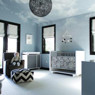Diseño de habitación de bebé neutra actual, de tamaño medio, con paredes azules