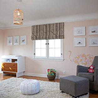 Idéer för att renovera ett vintage babyrum, med rosa väggar och mellanmörkt trägolv