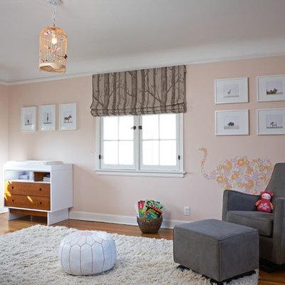 Transitional girl medium tone wood floor nursery photo in Los Angeles with pink walls