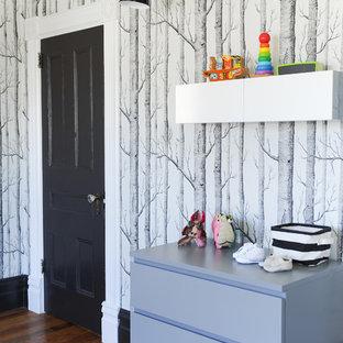 Modelo de habitación de bebé neutra bohemia, de tamaño medio, con paredes blancas y suelo de madera en tonos medios