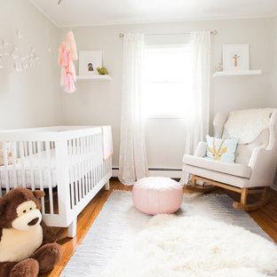 Modelo de habitación de bebé niña clásica renovada, de tamaño medio, con suelo de madera en tonos medios