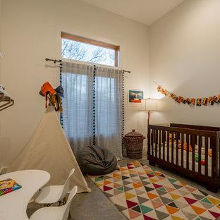 Inspiration för moderna könsneutrala babyrum, med vita väggar och betonggolv