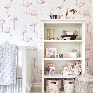 Imagen de habitación de bebé niña tradicional renovada, de tamaño medio, con paredes rosas, suelo de madera en tonos medios y suelo marrón