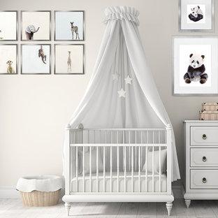 Modelo de habitación de bebé neutra tradicional renovada con paredes beige, suelo de madera clara y suelo blanco