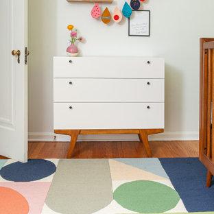 Cette image montre une petit chambre de bébé fille vintage avec un mur vert, un sol en bois brun et un sol multicolore.