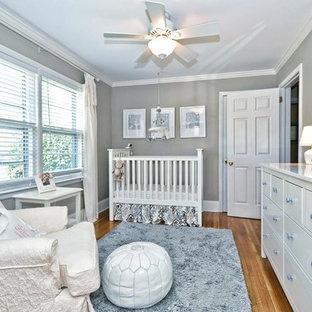 Modelo de habitación de bebé neutra clásica con paredes grises y suelo de madera en tonos medios