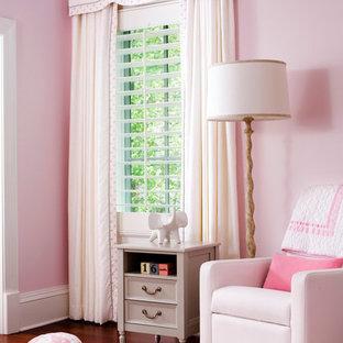 Klassisk inredning av ett mellanstort babyrum, med rosa väggar och mörkt trägolv