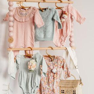 Exemple d'une chambre de bébé fille éclectique avec un mur blanc, moquette, un sol multicolore et un mur en parement de brique.