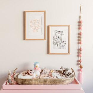 Inspiration pour une chambre de bébé fille bohème avec un mur blanc, moquette, un sol multicolore et un mur en parement de brique.