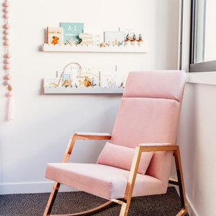 Пример оригинального дизайна: комната для малыша в стиле фьюжн с белыми стенами, ковровым покрытием, разноцветным полом и кирпичными стенами для девочки