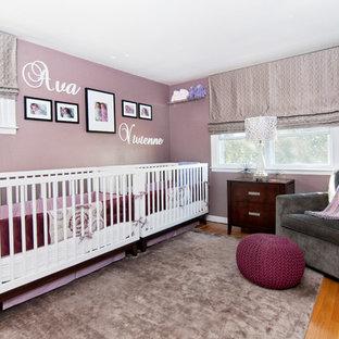 Ejemplo de habitación de bebé niña actual, de tamaño medio, con paredes púrpuras y suelo de madera clara