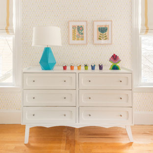 Imagen de habitación de bebé neutra clásica renovada con suelo naranja