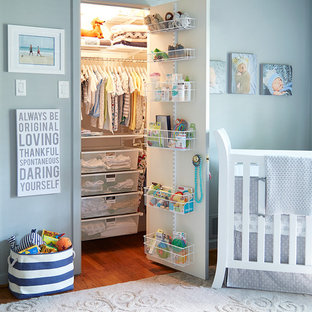 Photo of a traditional nursery for boys in Dallas with blue walls and medium hardwood flooring.