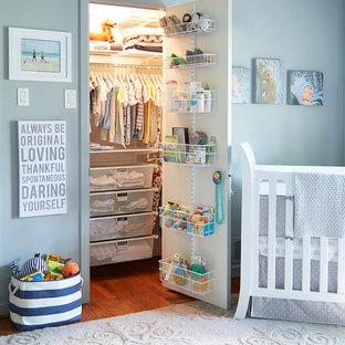 Cette photo montre une chambre de bébé garçon chic avec un mur bleu et un sol en bois brun.