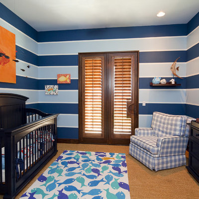 Mid-sized trendy boy carpeted nursery photo in Austin with blue walls