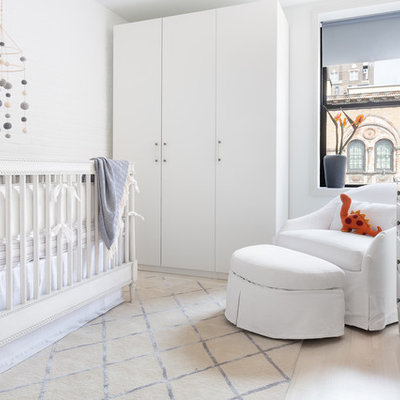 Inspiration for a mid-sized contemporary boy light wood floor and beige floor nursery remodel in New York with gray walls