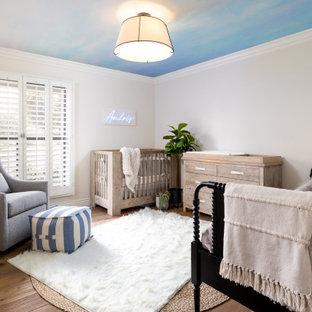 Cette image montre une chambre de bébé garçon traditionnelle de taille moyenne avec un mur bleu, un sol en bois clair et un sol marron.