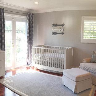 Ispirazione per una cameretta per neonato di medie dimensioni con pareti grigie e pavimento in legno massello medio