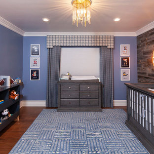 This is an example of a classic nursery for boys in Los Angeles with blue walls, dark hardwood flooring and brown floors.