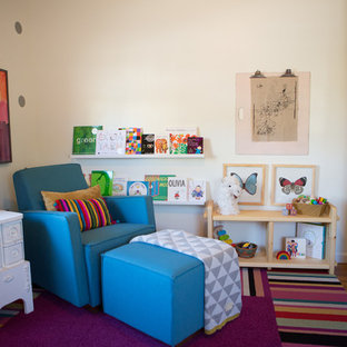 Photo of a medium sized eclectic nursery for girls in San Diego with white walls and medium hardwood flooring.
