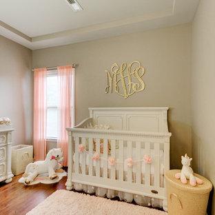 Imagen de habitación de bebé niña romántica, pequeña, con paredes grises, suelo de madera en tonos medios y suelo marrón
