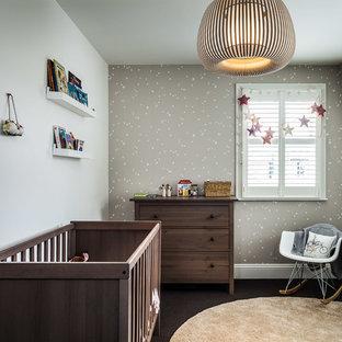 Modelo de habitación de bebé neutra clásica renovada con paredes grises, moqueta y suelo marrón