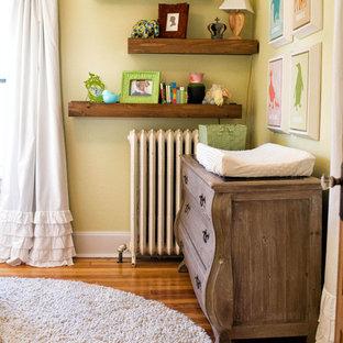 Diseño de habitación de bebé neutra clásica renovada, pequeña, con paredes amarillas y suelo de madera en tonos medios